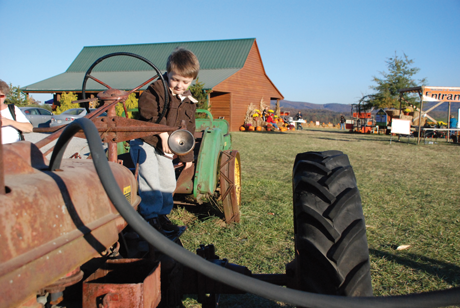 Child on a tractor at a farm.