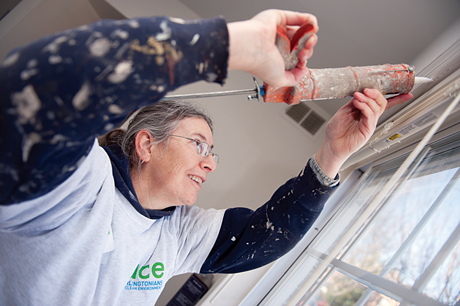 An Energy Masters Program volunteer caulks a window to prevent drafts and keep moisture from rotting the wood around the window.