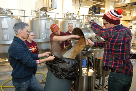A student spoons spent grain from the brewhouse container into a trash can while classmates look on. The professional-grade brewhouse is similar to what most craft-beer-making facilities use, but it is optimized for teaching.