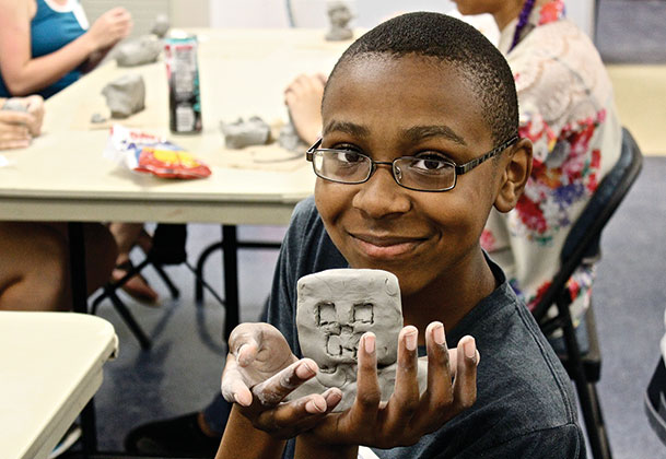 "During military art camp, a participant proudly displays a clay ""creeper"" figure he created."