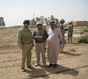 Mark Mitchell is an agricultural consultant who has worked all over the world overseeing production and supply chain systems. Here Mitchell (left), his interpreter (center), and an Iraqi farmer (right) stand near newly established drip irrigation lines.