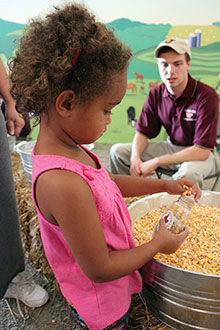 Members of the Ag Econ/NAMA club give away grain jars and educate children about agriculture at the 2013 State Fair of Virginia.