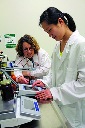Joell Eifert (left) shows graduate student Moonyoung Choi how to conduct food safety tests.