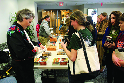 Temple Grandin signs books after speaking to a standing room-only crowd at the Virginia Bioinformatics Institute.