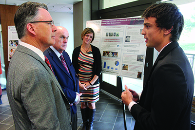 Jacob Cantor (right) presents a poster to Virginia Tech President Timothy Sands (left) Provost Mark McNamee, and Erin Ling, coordinator of the Virginia Household Water Quality Program, that illustrates the results of his outreach on the Eastern Shore.