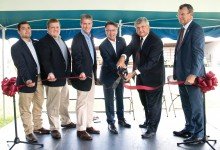 Six men cut a red ribbon with oversized scissors.