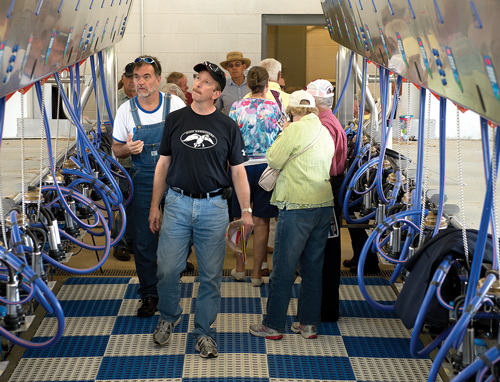People tour a milking parlor at a dairy.