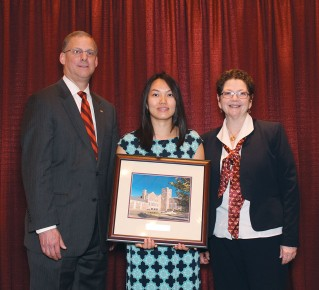 Grant and Debbie Day, (right) the university's associate vice president of alumni relations, present Anh Trahn with the Outstanding Recent Alumni Award.