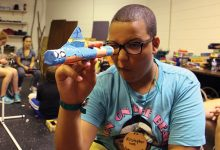 A student examines a homemade rocket
