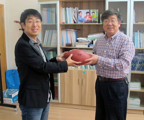 Yufeng Zou, left, presents Pute Wu with a Virginia Tech football.