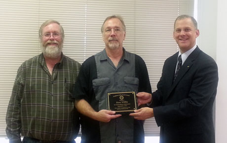 Ross Willis, center, receives his award from biochemistry department head Peter Kennelly, left, and Dean Alan Grant.