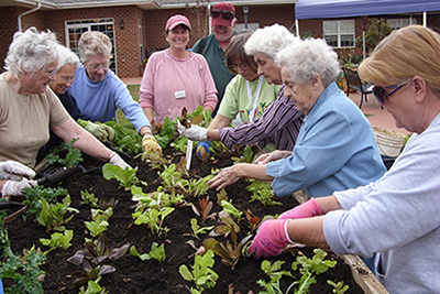 Bedford Master Gardeners help residents plant a spring raised bed.