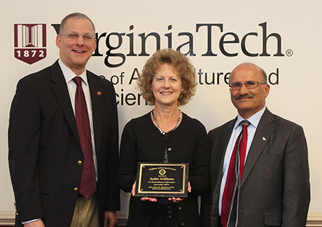 Robin Williams receiving her Employee of the Month award from Dean Alan Grant (left) and Saied Mostaghimi
