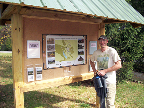 Kyle Peer, superintendent of the Reynolds Homestead Forest Resources Research Center, is shown with the LEAF Trail kiosk he constructed. The kiosk is used by hundreds of visitors, students, and hikers each year who can learn about the site's forestry research as well as the history of the Reynolds Homestead.