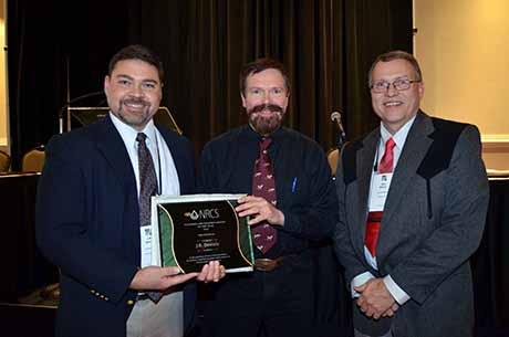 J.B. Daniel receives his award after being selected as the American Forage and Grassland Council's Pastureland Conservationist of the Year